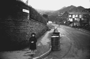 A young survivor stands at the corner of Moy Road; behind her, a scene of complete ruin.
